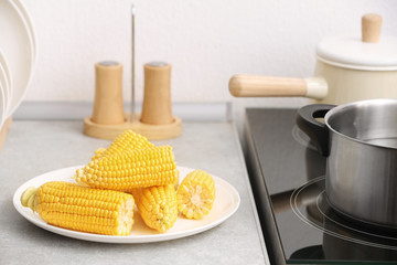 Plate with ripe corn cobs on kitchen table