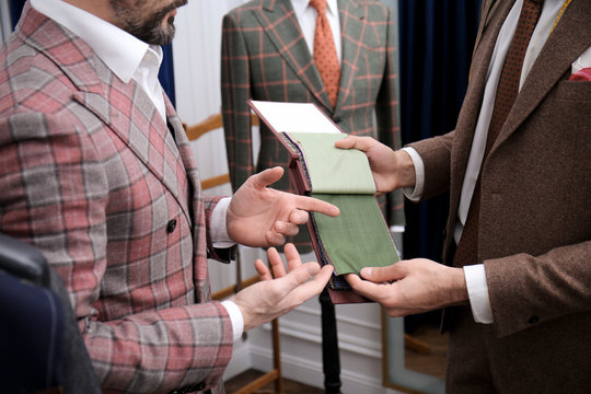 Tailor with client in atelier. Choosing fabric for custom made suit