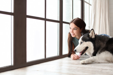 Young woman with cute Husky dog near window at home. Pet adoption