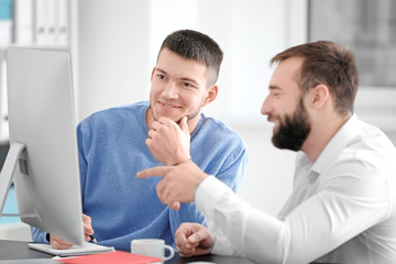 Marketing expert working with young trainee at table
