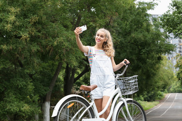 Attractive woman taking selfie near bicycle outdoors