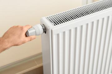 Man adjusting heating radiator thermostat indoors