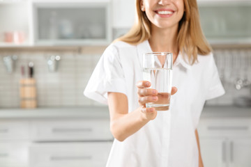 Young woman holding glass with clean water in kitchen, closeup