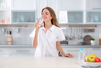 Young woman drinking clean water from glass in kitchen
