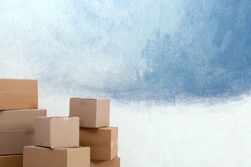 Cardboard boxes near color wall. Mockup for design