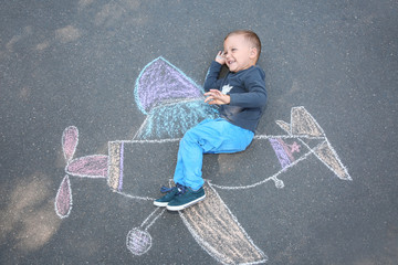 Little child lying near chalk drawing of airplane on asphalt, top view