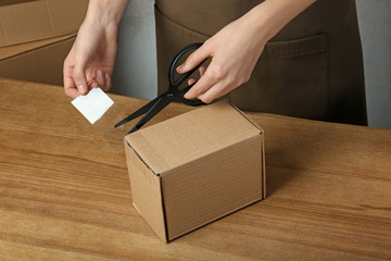 Woman packing box at table, closeup. Space for design