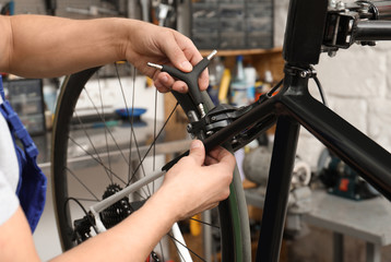Professional mechanic repairing bicycle in modern workshop, closeup