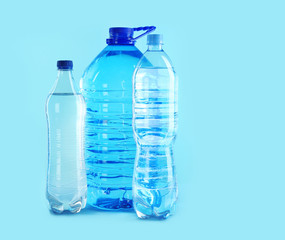 Different plastic bottles with pure water on color background. Space for text