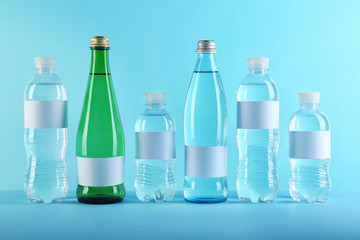 Different bottles of pure water with blank tags on color background