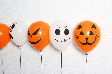 Color balloons for Halloween party against white brick wall