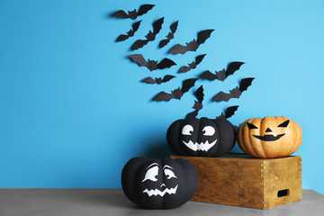 Set of Halloween decorations on table against color background. Space for text