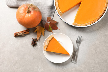 Flat lay composition with piece of fresh delicious homemade pumpkin pie on gray background