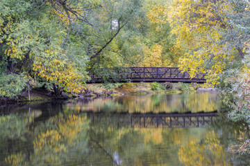 footbridge over a river in fall scenery