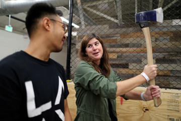 Teri Watson participates in axe throwing, a sport that started in the Canadian backwoods and is growing in popularity in U.S. cities, at LA Ax in North Hollywood, Los Angeles