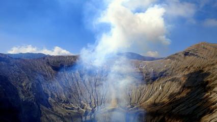 Kraterrand des Vulkans Bromo mit aufsteigendem Rauch in den blauen Himmel in Java Wall mural