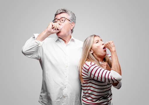 senior cool husband and wife Coughing, suffering a winter illness such as a cold or the flu, feeling unwell and feverish.