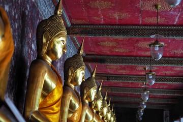 Arrangement of golden buddha statue in Thailand temple