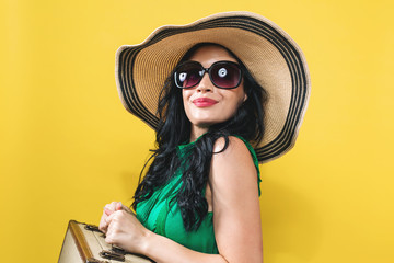 Young woman with a suitcase travel theme on a yellow background