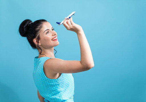 Young woman with toy airplane travel theme on a blue background