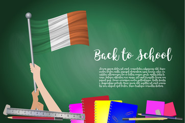 Vector flag of Ireland on Black chalkboard background. Education Background with Hands Holding Up of Ireland flag. Back to school with pencils, books