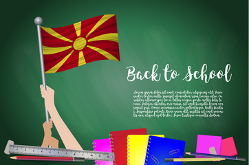Vector flag of Macedonia on Black chalkboard background. Education Background with Hands Holding Up of Macedonia flag. Back to school with pencils, books, school items learning and childhood concept.