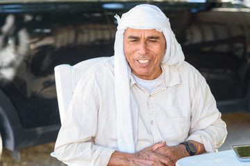 Old Arabic man in traditional clothes outdoor portrait.Smiling Muslim Senior business man on a desk.