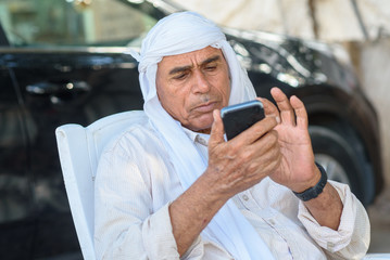 Muslim Senior businessman using a smartphone. Old Arabic man in traditional head clothes outdoor portrait.