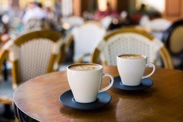 Cups of cappuccino with latte on wodden table.