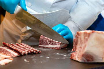 butcher or chef are cutting and decorating highest  meat grade of marbling A5 japanese wagyu beef for barbecue menu and sell in japanese restaurant or butcher shop in japan.