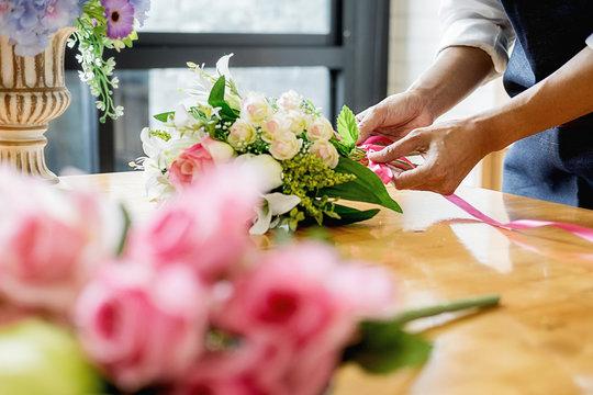 Woman hands making flower composition at florist workshop. Do it yourself concept