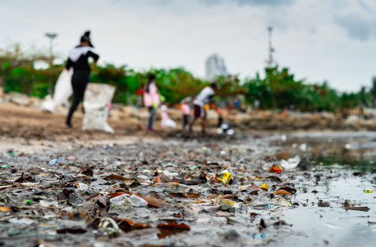 Blurred of volunteers collecting garbage. Beach environment pollution. Volunteers cleaning the beach. Tidying up rubbish on beach. Oil stains on the beach. Oil leak to the sea.