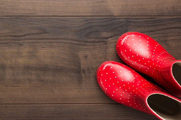 new red children's stylish gumboots with some copy space. overhead shot of watertights on wooden floor