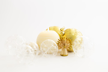 Still life with beautiful decorative transparent and gold colored christmas glass balls, a round satin colored burning candle, a satin star ornament and a straw angel on white background