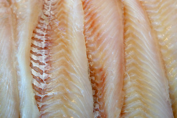 Cut fillet of fish on the counter