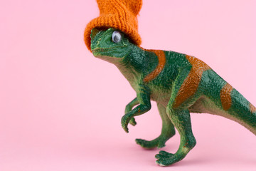 funny green dinosaur toy in little knitted orange hat  near on pastel pink background