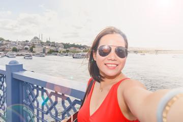 Beautiful woman takes selfie over Galata Bridge