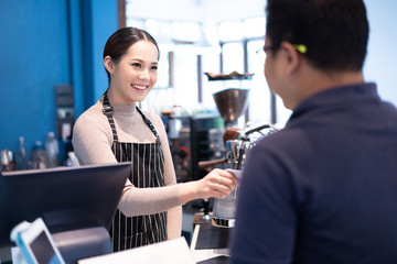 Asian women barista accept credit cards from customers in the coffee shop.
