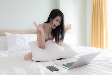 Young asian girl very happy shopping online on laptop wifi internet connection on white bed in the bedroom on weekends