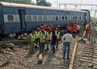 Rescuers stand besides a damaged coach of a passenger train after it derailed in Harchandpur