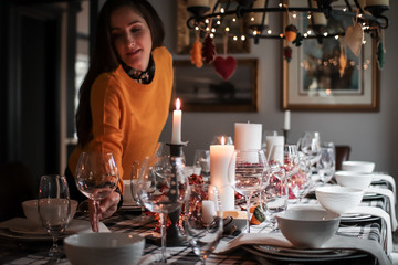 Young woman placing wine glass on holiday dinner table