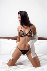 Sexy slim woman posing on her bed