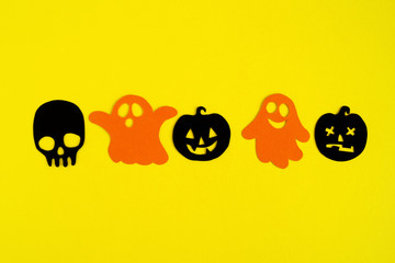 Holiday decorations for Halloween. Orange paper ghosts and black paper pumpkins and skull on a yellow background, top view.