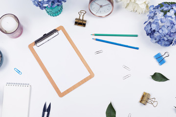 Feminine desk workspace frame mockup with beauty arrangement of bouquet hydrangeas, clipboard, notebook, pencil and candle on white background with copy space. Flat lay, Top view.