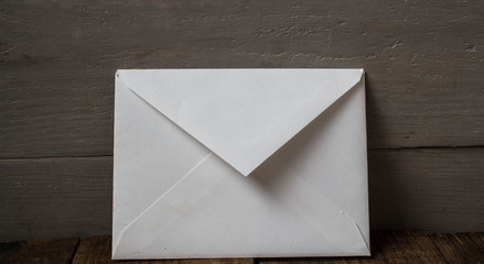 a white envelope on grey wooden background
