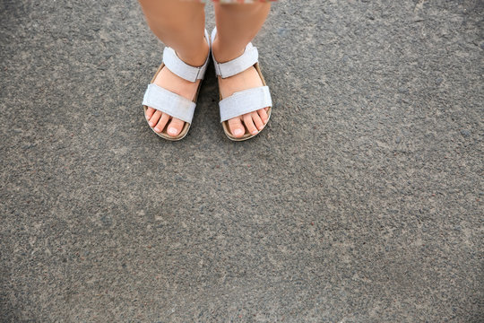 Legs of girl wearing sandals outdoors