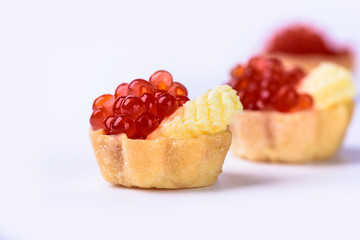 Several tartlets with red caviar and butter isolated on white background