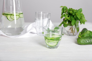 Glass of tasty fresh cucumber water on white table