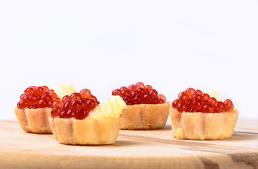 Tartlets with red caviar and butter on a cutting board