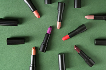 Lipsticks of different shades on color background